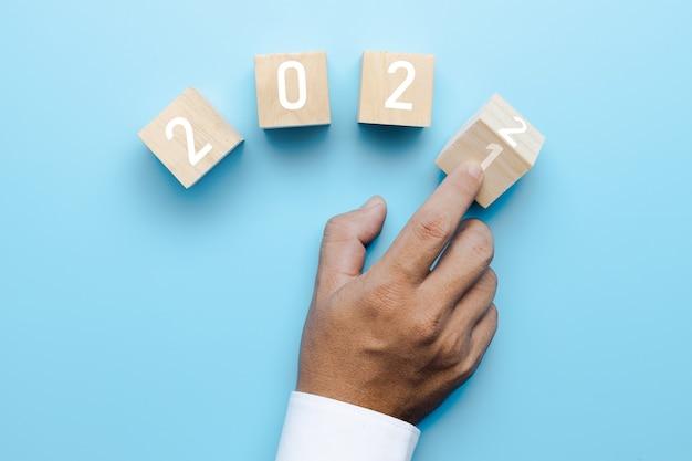 La mano de la gente de negocios cambia de 2021 a 2022 en la caja del cubo
