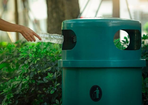 Mano de la gente que lanza la botella de agua vacía en papelera de reciclaje en el parque. papelera de reciclaje de plástico verde. hombre descartar botella en la papelera