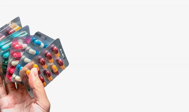 La mano de la gente que sostiene el paquete de píldoras antibióticas de la cápsula aisladas. dar o recibir drogas. resistencia a los medicamentos antimicrobianos. producto farmacéutico. cuidado de la salud.