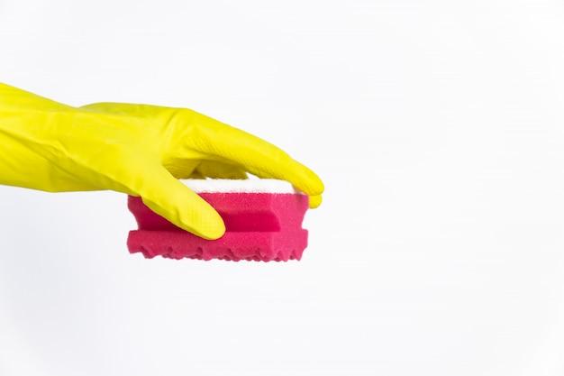 Mano con guante amarillo con esponja roja para limpiar