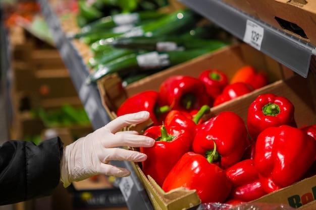 Mano en un guante blanco lleva pimiento rojo en una tienda. seguridad epidémica