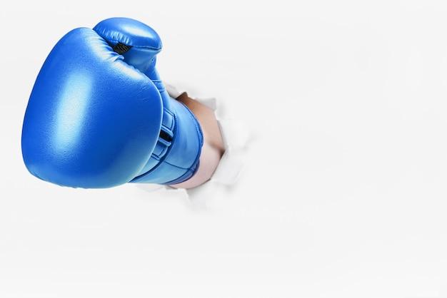 Mano en guante de boxeo atravesó la pared de papel