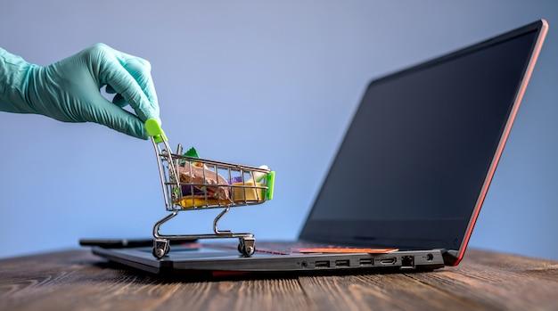 La mano en un guante estéril sostiene un carrito de compras con una tarjeta de crédito. compra por internet durante la pandemia de coronavirus