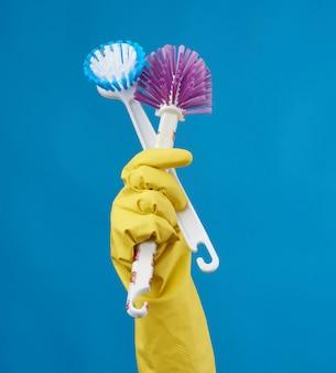 Mano en un guante de goma amarillo para limpiar una casa sostiene dos cepillos de plástico