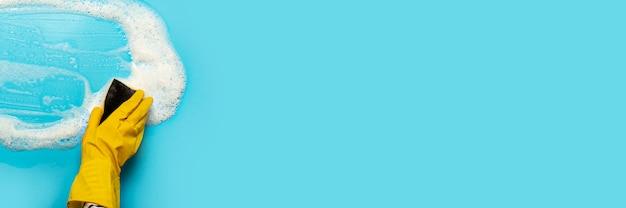 La mano en un guante de goma amarillo sostiene una esponja limpiadora y limpia una espuma jabonosa sobre una superficie azul. concepto de limpieza, servicio de limpieza. . vista plana, vista superior