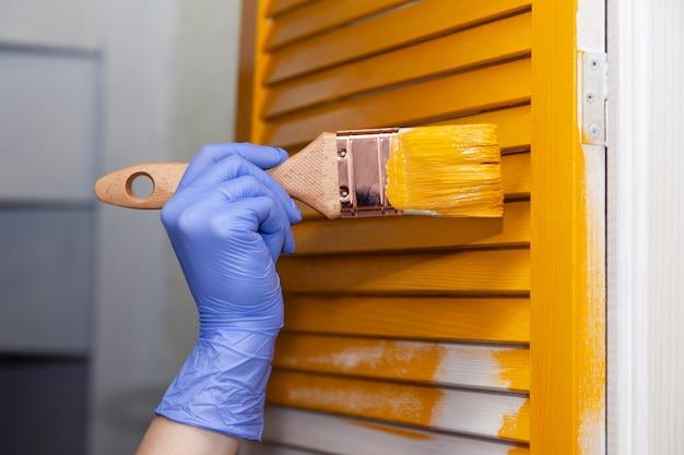 Mano en guante de goma azul con pincel pintando puerta de madera natural con pintura amarilla
