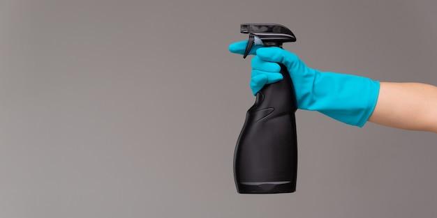 Una mano en un guante de goma azul sostiene el limpiador de vidrios en una botella de spray