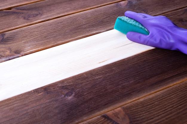 Una mano en un guante de goma lava una superficie de madera. limpieza, limpieza de habitaciones.