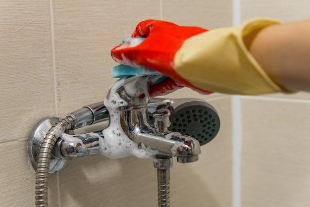 La mano en el guante de goma limpia el grifo mezclador de ducha calcificado sucio, foto de primer plano