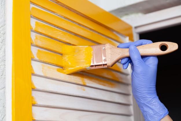 Mano en guante de goma púrpura con pincel pintando puerta de madera natural con pintura amarilla