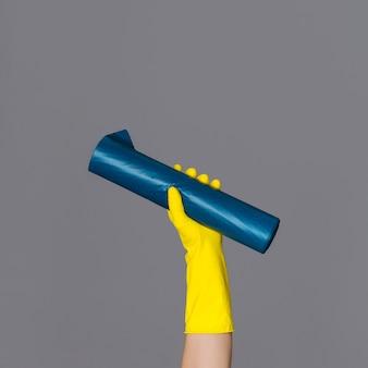 La mano en el guante de goma sostiene una bolsa de basura azul sobre fondo neutro. el concepto de limpieza de primavera.