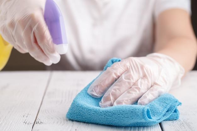La mano en un guante de goma sostiene una botella de spray de detergente líquido. limpieza
