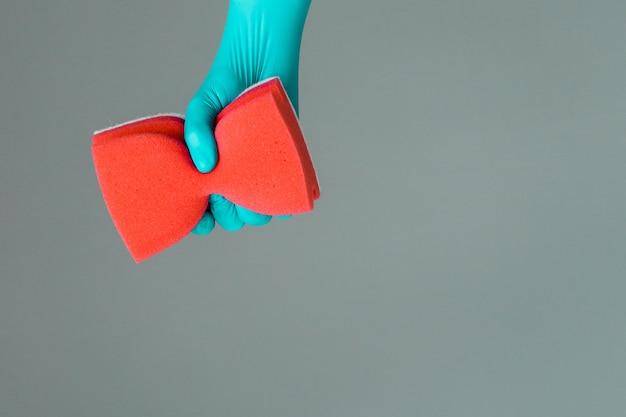 Mano en guante de goma sostiene color esponja de lavado. el concepto de primavera brillante, limpieza de primavera.