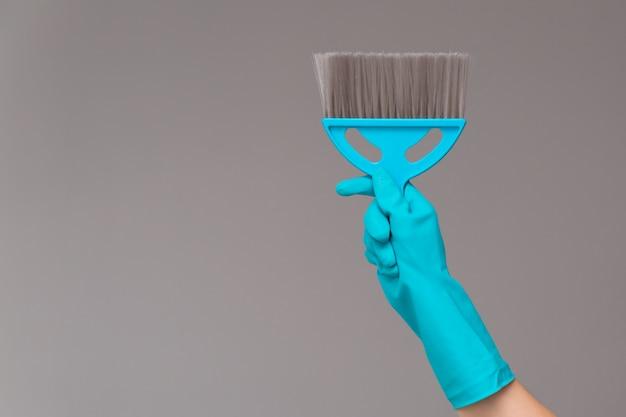 Una mano en un guante de goma sostiene una panícula en gris