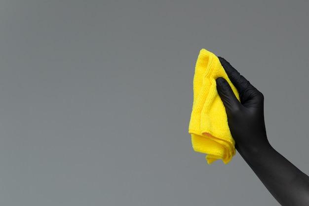 Una mano en un guante de goma sostiene un plumero de microfibra brillante