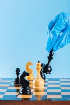Mano en guante jugando al ajedrez con peones de madera