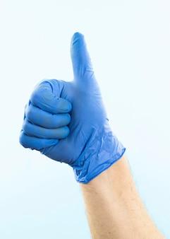 Mano con guante de látex mostrando los pulgares para arriba
