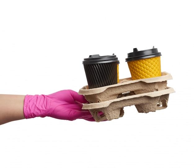 La mano en un guante de látex rosa sostiene una bandeja de papel con vasos de cartón desechables y cubiertas de plástico.