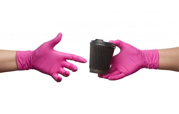 La mano en un guante de látex rosa tiene una taza de cartón desechable de papel