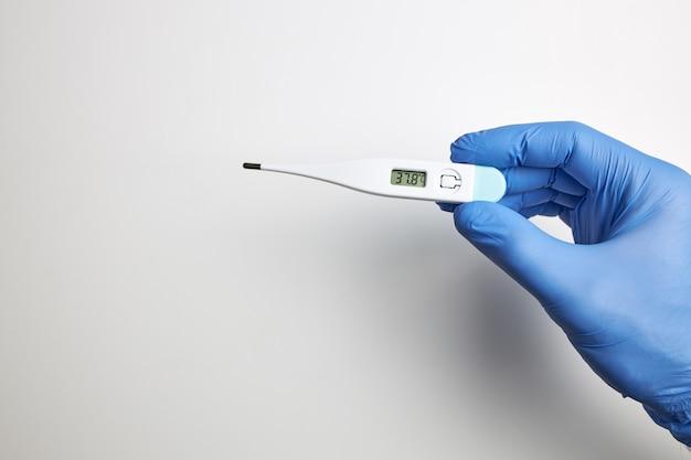 Mano con guante de látex con termómetro digital que marca la temperatura alta.