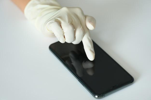 Mano con guante médico tocando smartphone en enfoque selectivo
