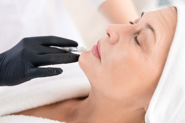 Mano en guante negro de cosmetóloga haciendo inyección de aumento de labios a mujer madura