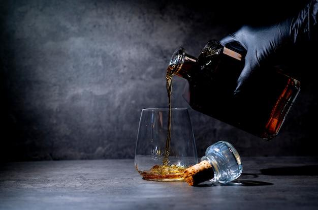 Mano en un guante negro vierte whisky de una botella cuadrada en un vaso sobre una superficie de cemento gris oscuro