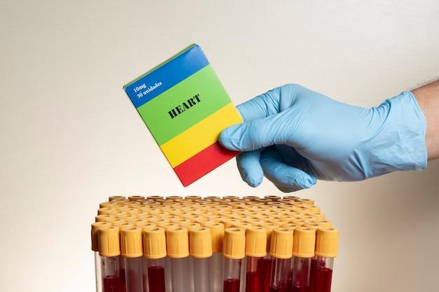 Mano con guante protector de nitrilo con caja de medicina con tubos de extracción de sangre.