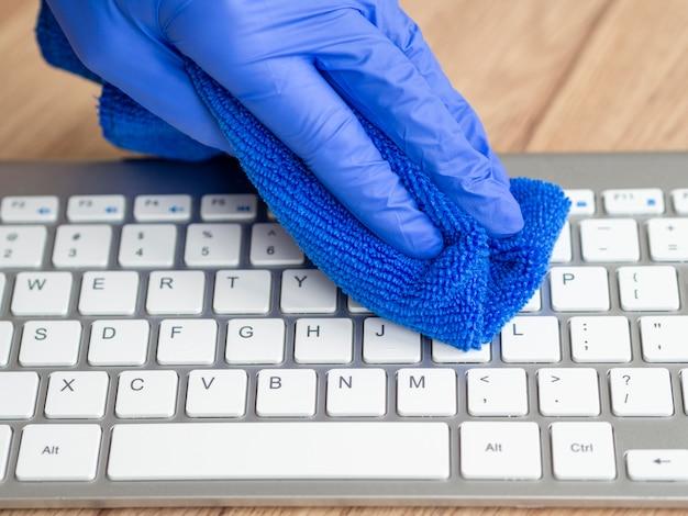Mano con guante quirúrgico, teclado de limpieza con paño