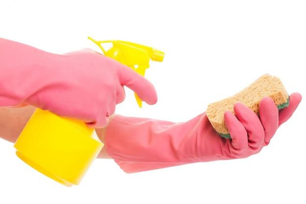 Mano en un guante rosa con spray y esponja