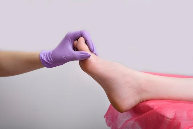 La mano en el guante sostiene la pierna femenina después de la pedicura. salón de belleza