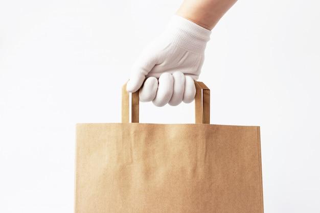 La mano en un guante tiene una bolsa de cartón marrón aislada