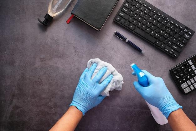 Mano en guantes de goma azul sosteniendo la botella de spray y limpiando la superficie plana