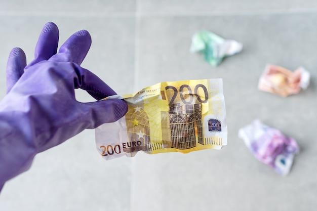 Mano en guantes de goma violeta para limpiar sosteniendo billetes de euro arrugados en gris