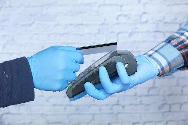 Mano en guantes médicos pago sin contacto con tarjeta de crédito