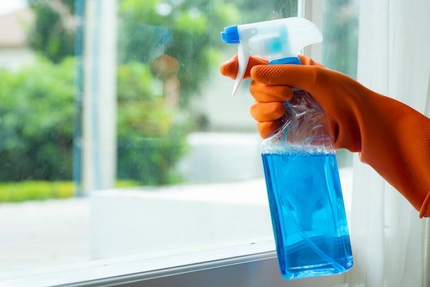 Mano en guantes naranjas, limpieza del cristal de la ventana con spray concepto de limpieza prevenir diversas infecciones por virus