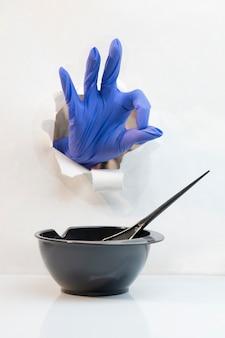 La mano en guantes de peluquería azules a través de un agujero muestra el gesto todo bien y el tazón negro con un cepillo