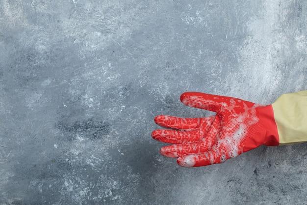 Mano en guantes protectores sobre mármol.