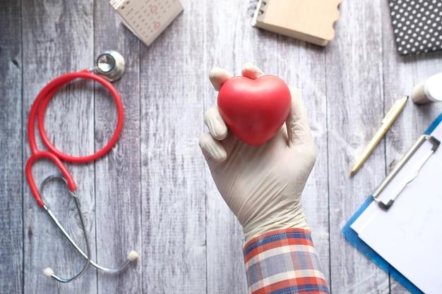 Mano en guantes protectores sosteniendo corazón rojo sobre azul