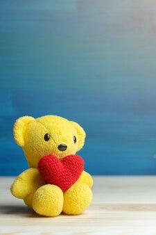 Mano hacer hilo corazón rojo puesto en oso de peluche amarillo