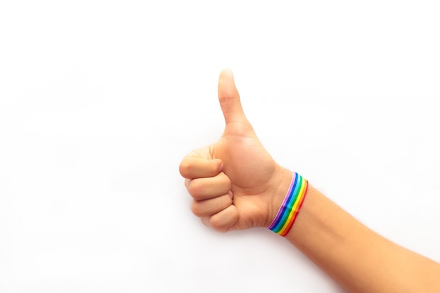 Mano haciendo bien gesto con pulsera lgbt aislado sobre fondo blanco.
