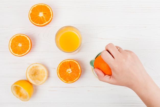 Mano haciendo jugo de naranja