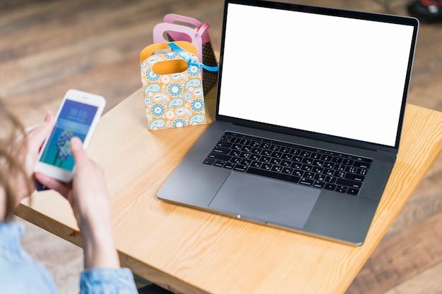 La mano de la hembra que sostiene smartphone con el ordenador portátil de la pantalla en blanco en la tabla de madera
