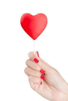 Mano hermosa de la mujer con el clavo rojo que sostiene la piruleta roja del corazón aislada en el fondo blanco