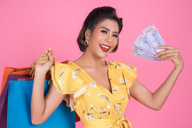 Mano hermosa de la mujer de la moda feliz que sostiene el dinero del dólar para hacer compras