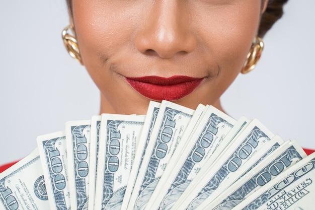 Mano hermosa de la mujer de la moda feliz que sostiene el dinero del dólar