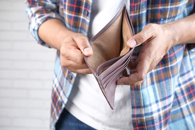 Mano de hombre abre una billetera vacía con espacio de copia