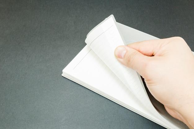 La mano de un hombre abriendo un libro.