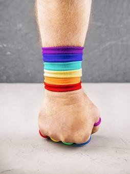 La mano del hombre apretada en un puño con un brazalete de colores del arco iris golpea un muro de hormigón, concepto de protección de los derechos de las personas lgbt, orgullo