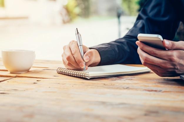 Mano del hombre de asia que escribe el papel del cuaderno y que usa el teléfono en la tabla de madera en cafetería con el filtro tonificado de la vendimia.